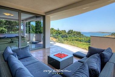 Covered outdoor lounge area with sea view in beautiful villa in Premantura