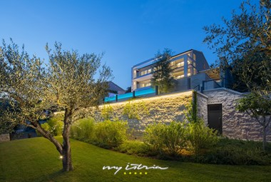 Villa Vlastelini II by night viewed from the garden with olive trees
