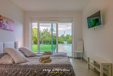 Bedroom in villa Heike with slide doors to the pool
