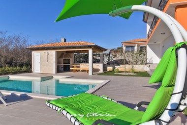 Sun lounger with sunshade next to the pool