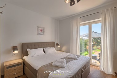 Bedroom with double bed and balcony with view over the pool area - Villa Laura An