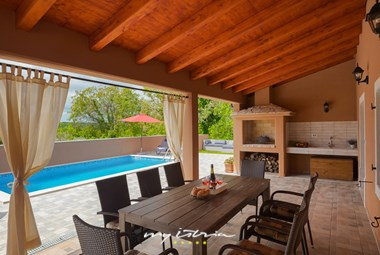 Dining table and barbecue on villa´s covered terrace