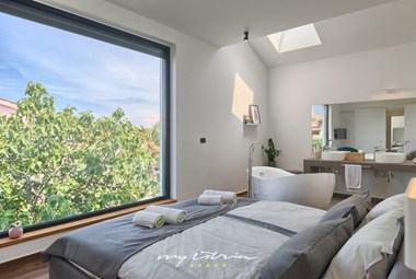 Comfortable bedroom with a relaxing view on the greenery in Villa Buza