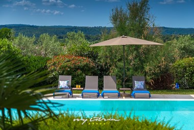 Green garden of Villa Naturavita and sun loungers next to the pool