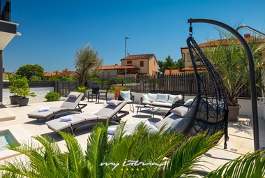 Garden furniture and sun loungers to unwind next to the private pool of Villa Orion