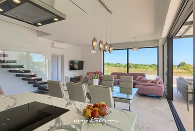 Modern living space with dining area and large balcony doors - Villa Sunshine Tea