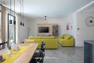 Bright and modernly furnished living room with dining area and kitchen in Villa Perle