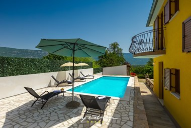 Outdoor area around the pool with sun loungers to unwind and relax in villa Mikales