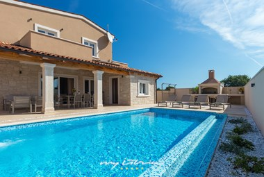 Long swimming pool with nice outdoor area surrounding villa Rafo in Pula