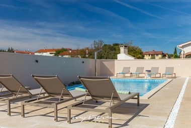 Sun loungers for relaxation and sun bathing next to the pool of villa Rafo near Pula