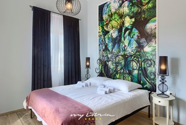 Stylishly decorated bedroom with a double bed and a balcony