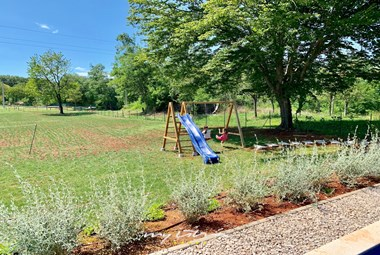 Playground for small guests with slide and slings in the garden of Villa Meadow near Labin
