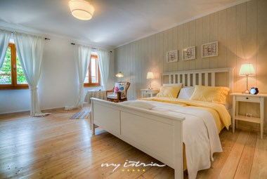Stylishly decorated bedroom with double bed in the villa