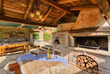 The spacious summer kitchen with a traditional open fireplace, bread oven and large al fresco dining area
