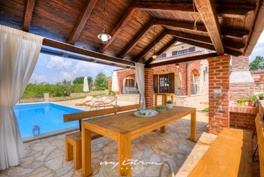 Covered terrace with dining area in front of the villa