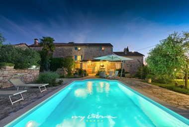 Illuminated private pool in front of the villa by night