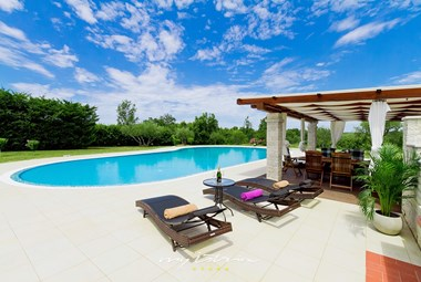 Sun loungers in front of villa´s beautiful pool