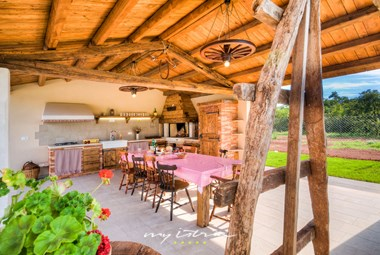Covered terrace with a rustic outdoor kitchen with dining space in our villa in Istria