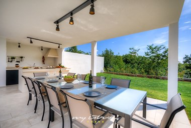 Covered outdoor kitchen with a dining room in the villa's beautiful garden