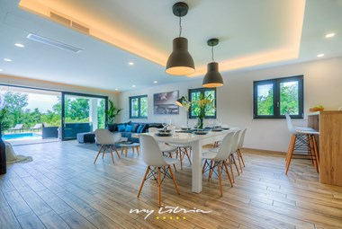 Modern open plan living area with access to the villa's pool