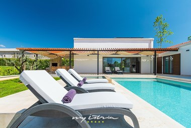 Sun loungers next to villa´s pool