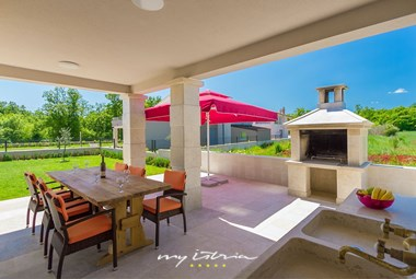 Covered dining area with barbecue in front of Villa Anzela
