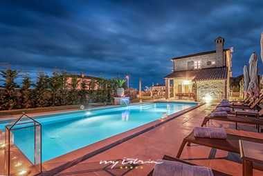 The beautiful villa with illuminated pool area by night