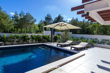Sun loungers and umbrellas by the pool in the completely enclosed garden of villa Bianca