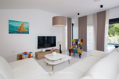 Bright and pleasant living room with Tv and balcony doors leading to the pool in villa Bianca