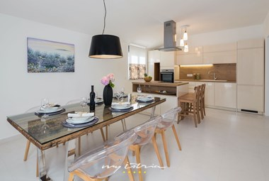 Modern fully-equipped kitchen with breakfast peninsula and elegant dining area in villa Bianca