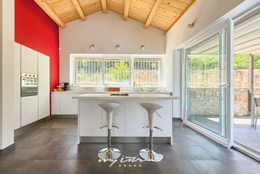Bright and modern fully-equipped kitchen with breakfast island and balcony doors in villa Paljari