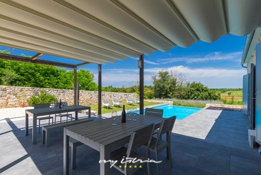 Outdoor dining area by the pool and view of the surrounding countryside in villa Paljari