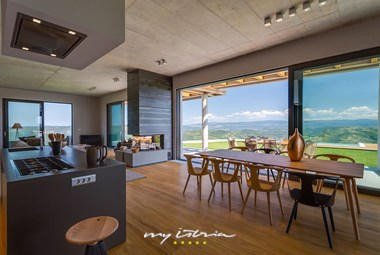Modern open space kitchen, living and dining area with large balcony doors with stunning panoramic view of the surroundings and nature in villa Vista