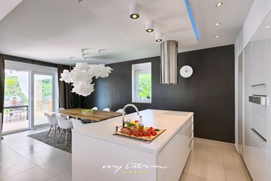 Modern fully equipped kitchen with a cooking island on the ground floor of the villa