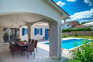 Inviting pool area of the villa with dining space on the covered terrace