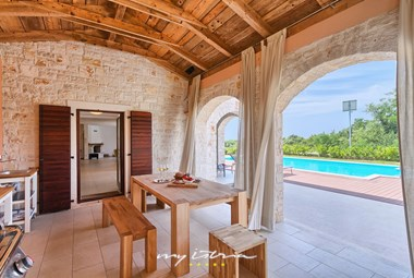 The villa has a covered outdoor kitchen and dining area