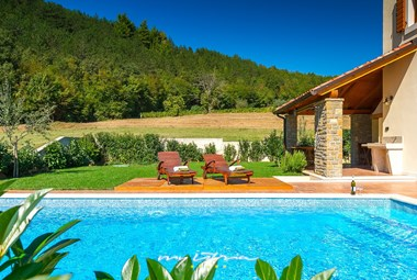 View of the pool and sun loungers surrounded by green nature in villa Penisola