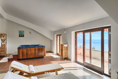 Jacuzzi with lounge area and large balcony doors overlooking the Kvarner bay in villa in Opatija
