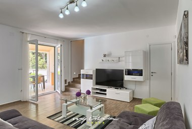 Modern living room with TV and balcony doors in Villa Lola