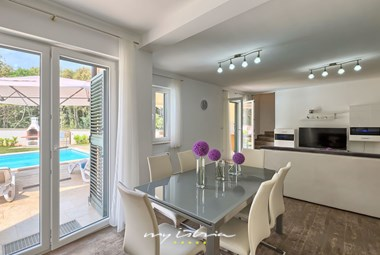 Fully equipped kitchen and dining are with balcony doors in Villa Lola