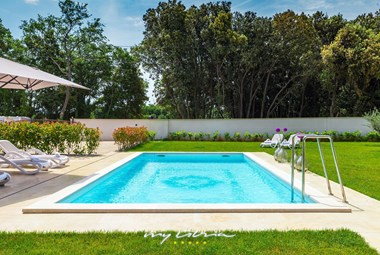 Private pool with sun loungers and umbrellas in villa in Pula