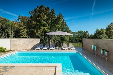 Enclosed private pool with sun loungers and umbrellas in villa Vita