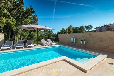 Enclosed private pool and sun loungers and umbrellas in villa in Pula