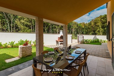 Covered outdoor eating area for 10 persons and traditional stone grill in villa Vita