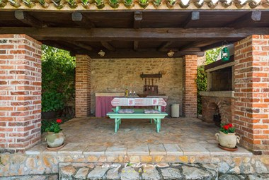 Outdoor dining area and kitchen with traditional stone grill in Villa Nini