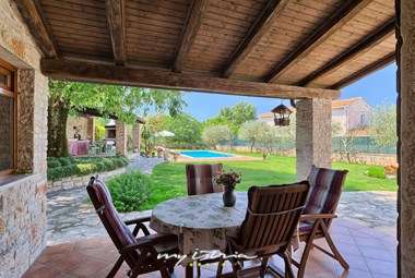 Covered terrace with dining table in villa with pool in Porec