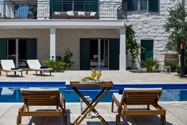 Relaxing sun loungers and drinks by the pool of villa Mir