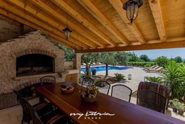 The incredibly relaxing outdoor dining area with a traditional open fireplace in our holiday villa with pool