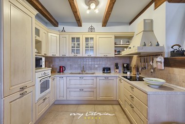 Bright and traditional kitchen with wooden beams and appliances in villa Karojba