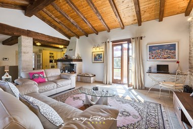 Cosy living room with a fireplace, writing spot and balcony doors leading to the garden of the villa